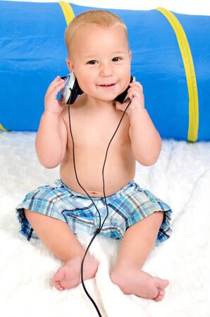 little happy boy listens to music with headphones photo