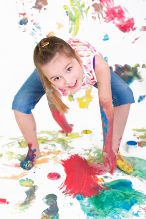 little girl painting with finger paints photo