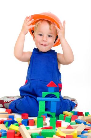 Kleine jongen met bouwvakker en bouwstenen