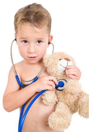 heart sounds: little boy examining a teddy bear with a stethoscope Stock Photo