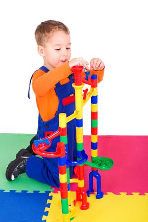 Kleiner Junge, den Aufbau einer Kugelbahn aus bunten Blöcken Standard-Bild - 34594400