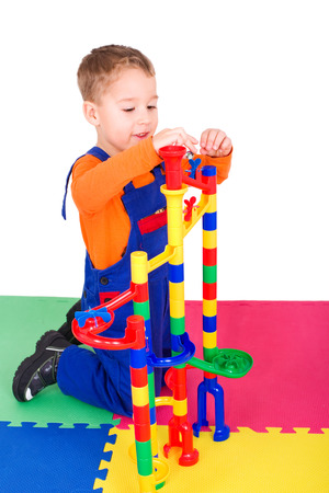 little boy building a marble run out of colorful blocks