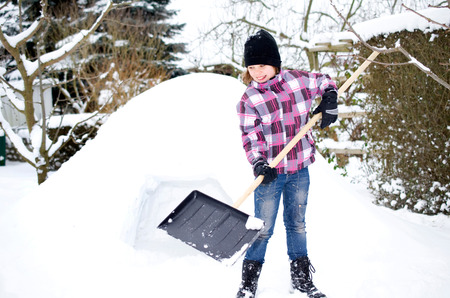 igloo: Girl with snow shovel in front of an igloo