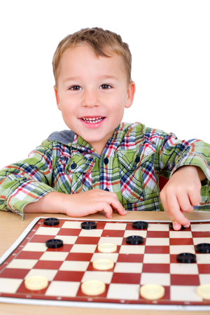 strategically: little boy plays checkers in front of a white background