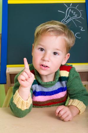undone: little boy put his hand up in school