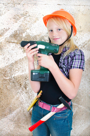 teen girl with a drill on a wall