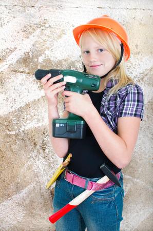 Teenager-Mädchen mit einem Bohrer an einer Wand Standard-Bild - 34791347