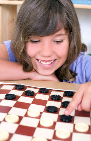 strategically: young girl plays checkers and smiles