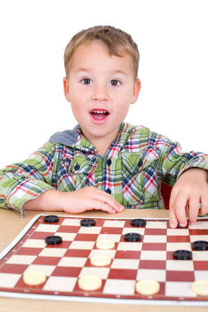 strategist: little boy plays checkers in front of a white background
