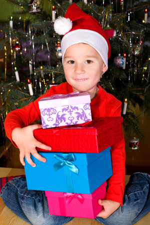 little boy with a lot of christmas gifts