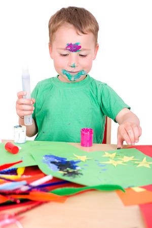 Kleiner Junge Basteln mit farbigen Papier, Leim und Lack Standard-Bild - 34832158