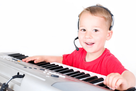 little boy with headset plays keyboards photo