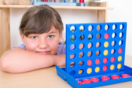 wins: young girl playing Connect Four and laughs into the camera Stock Photo