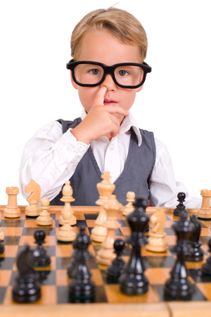 intellectually: little boy playing chess and picking his nose Stock Photo