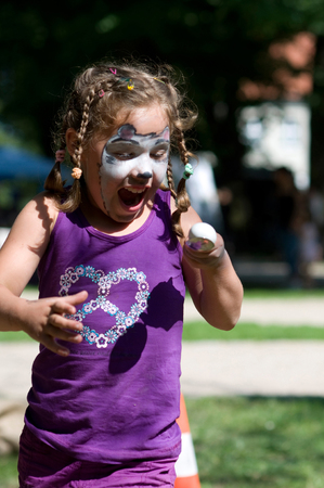 Girl with painted face plays egg and spoon race