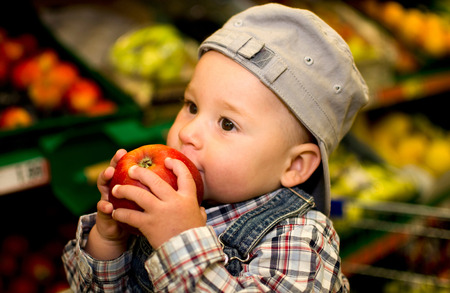 little boy eating an apple in the supermarket