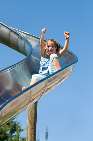 Girl on the slide with arms in the air and sing photo