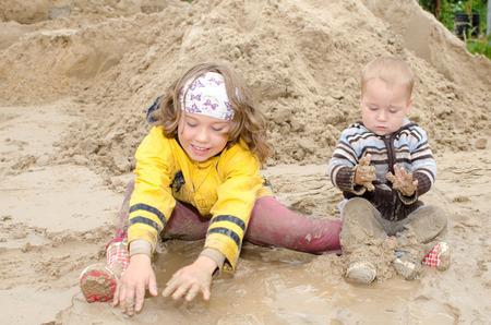 Kinderen zitten in een modderpoel en spelen