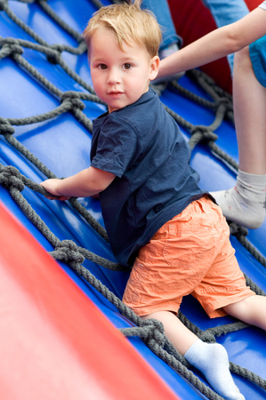 Little boy climbing on a net