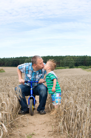 impeller: Father and son kissing in a corn field