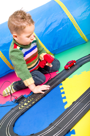 car race track: little boy playing with a car race track