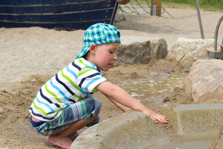 babyhood: little boy playing in the sandbox with water