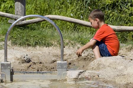 jongetje spelen in het zand met water Stockfoto