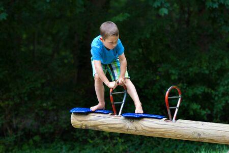 litttle boy climbing at a seesaw Zdjęcie Seryjne