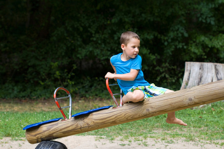 little boy sitting at a seesaw