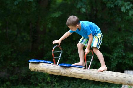 little boy climbing at a seesaw