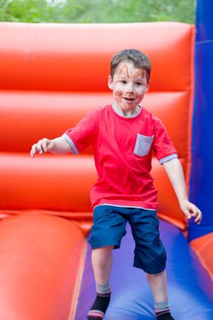 Junge springt auf einer Hüpfburg Standard-Bild - 44149865