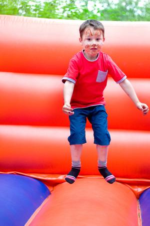 little boy jumping on a bouncy castle