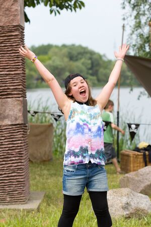 accuses: young girl accuses joy arms up in the air Stock Photo