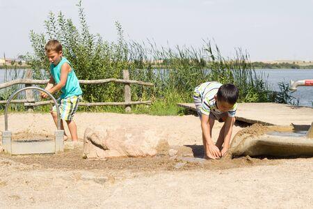 Jongens spelen in een speeltuin met water en zand Stockfoto