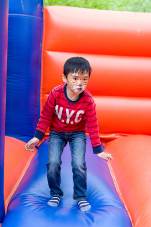 little boy jumping with colorful painted face on a bouncy castle
