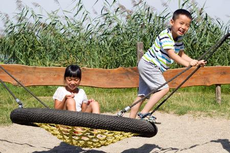 nido de pajaros: Hermanos que juegan en el oscilaci�n nido del p�jaro