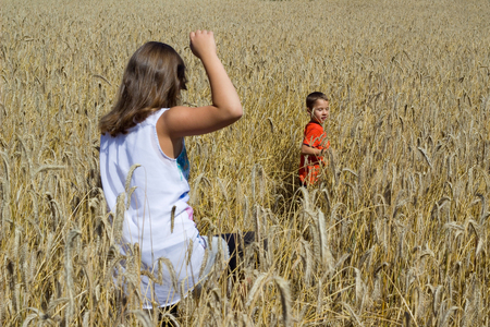 grasping: Siblings playing in the cornfield grasping