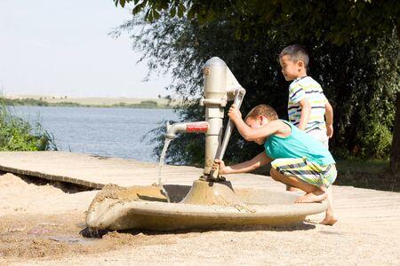 kleine jongens spelen met een waterpomp op het meer