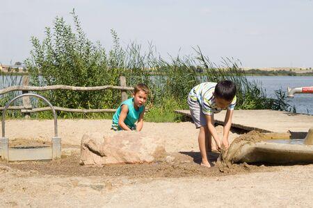 Kinderen spelen met water en zand bij het meer Stockfoto