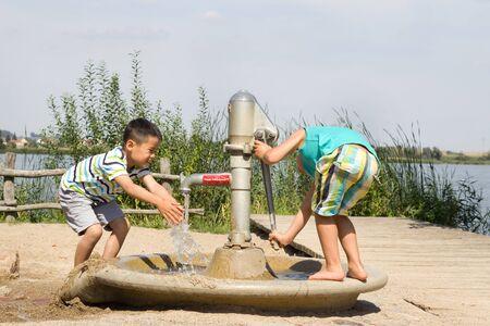 Kleine jongens pompen water in het meer