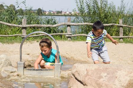 Kinderen spelen met water in het zand