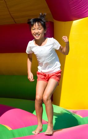 little girl jumping on a bouncy castle