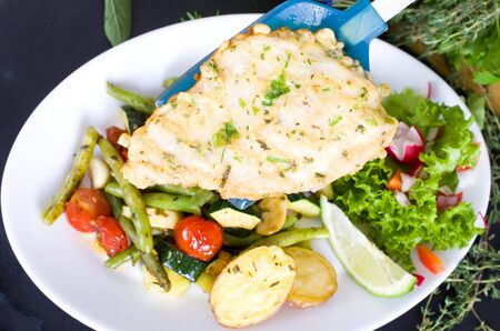 crust: cod fish with a herb crust on colorfull summer vegetables
