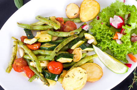 baked potatoes: Summer vegetable pan with baked potatoes on a bed of lettuce