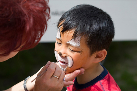 kids painting: little boy can be face painting to Tiger Stock Photo