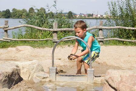 kleine jongen spelen met water en zand in een speeltuin