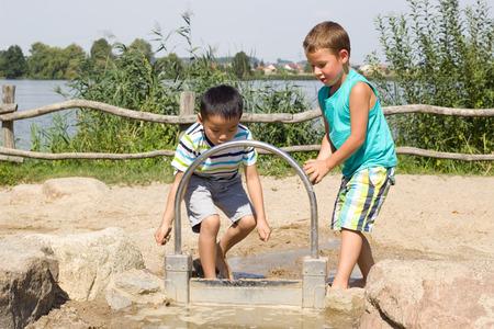 kleine jongens spelen met water in het zand