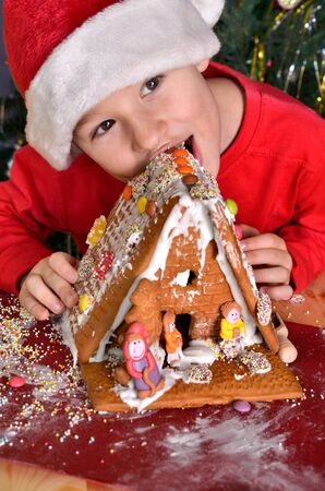 food stuff: little boy nibbling from gingerbread house for Christmas