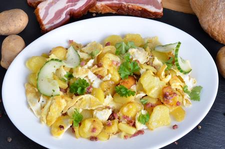 huevos revueltos: El desayuno del granjero, huevos revueltos con patatas, cebollas fritas y tocino Foto de archivo