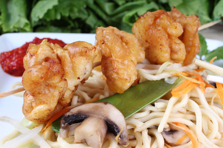 tans: fried noodles with vegetables and baked wontons on a spit Stock Photo